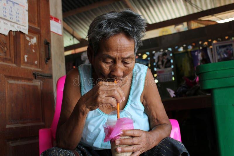 Grand-mère buvant une boisson dans la maison photo stock