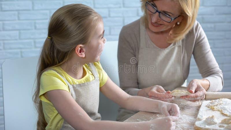 Grand-mère de aide de petite fille créative pour faire cuire la pâtisserie, recette traditionnelle photos libres de droits