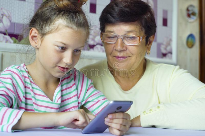 Grand-mère de enseignement de jeune petite-fille mignonne comment utiliser le smartphone à la maison photo stock