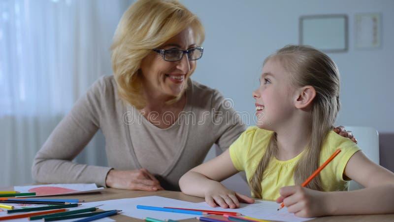 Grand-mère de sourire regardant sa peinture de petite-fille avec les crayons colorés photos stock