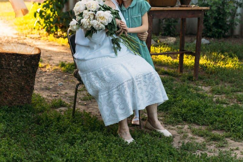 Grand-mère de visite grand-mère, femme agée reposant et étreignant sa petite-fille, fille et tenir un bouquet des fleurs dans photos libres de droits