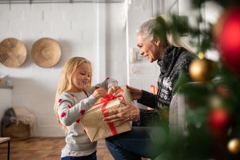 Grand-mère donnant le présent de Noël à la petite-fille photos stock