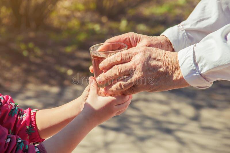 Grand-mère donnant un verre d'eau propre à un enfant image stock
