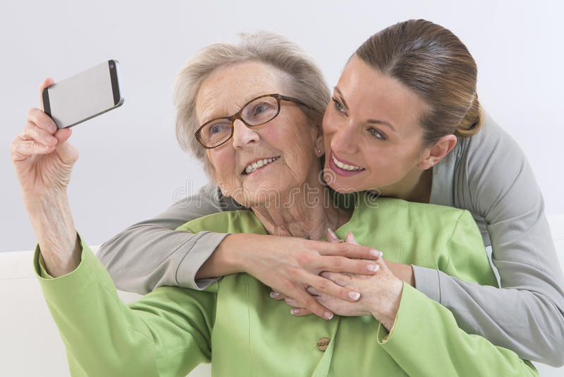 Grand-mère et jeune petite-fille se photographiant photos stock