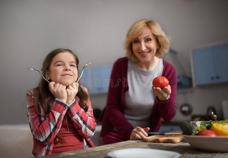Grand-mère et petite-fille mignonne faisant cuire la salade images libres de droits