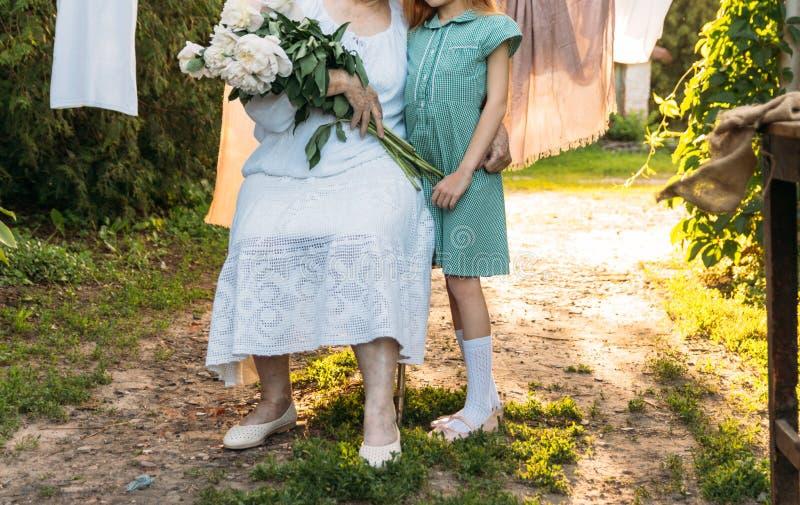 Grand-mère, femme agée reposant et étreignant sa petite-fille, fille et tenir un bouquet des fleurs dans le jardin images libres de droits