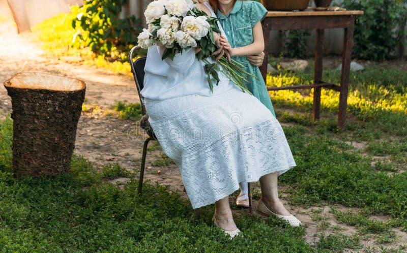 Grand-mère, femme agée reposant et étreignant sa petite-fille, fille et tenir un bouquet des fleurs dans le jardin photos stock