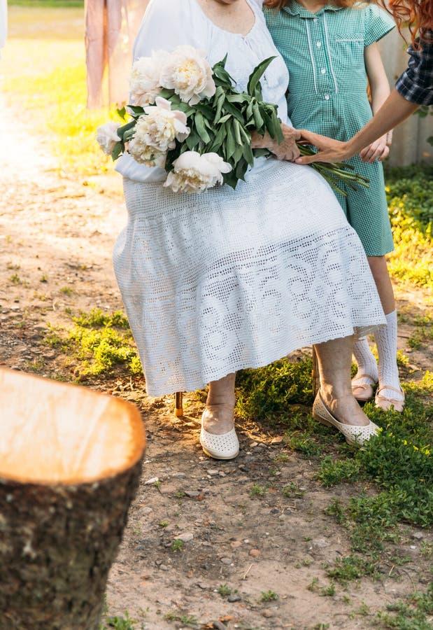 Grand-mère, femme agée reposant et étreignant sa petite-fille, fille et tenir un bouquet des fleurs dans le jardin un ha femelle photographie stock libre de droits