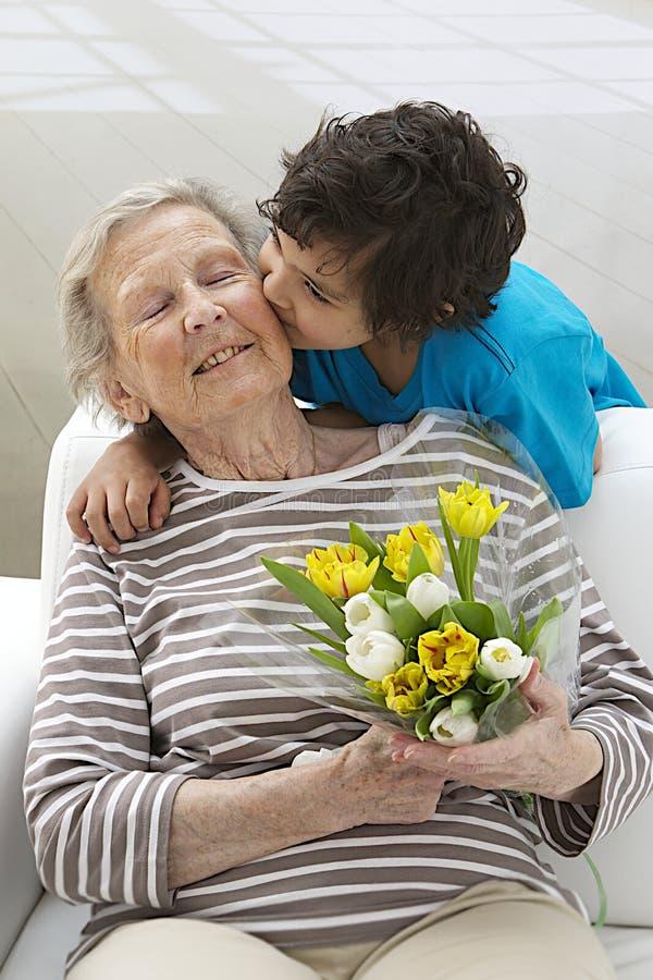 Grand-mère heureuse avec son petit fils avec des fleurs photo stock