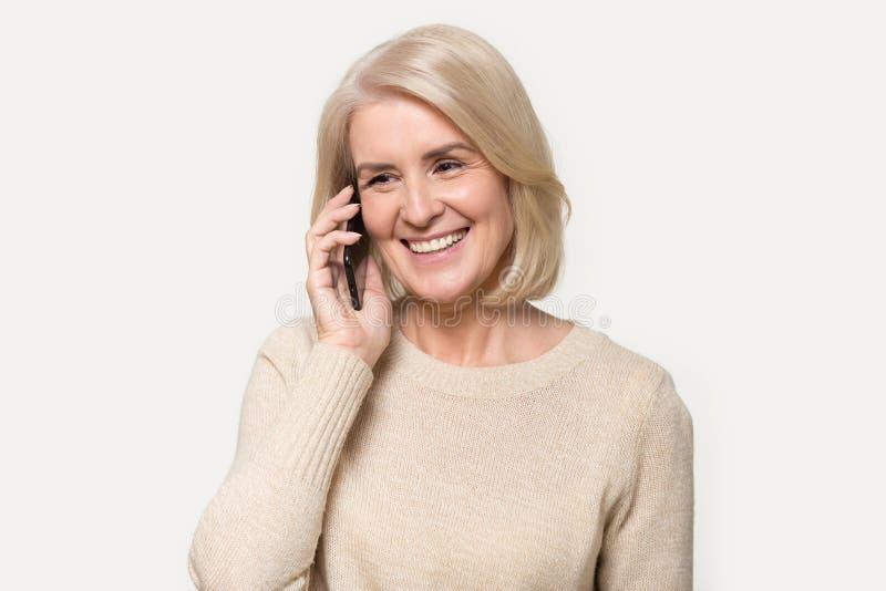Grand-mère heureuse parlant sur le téléphone portable avec le tir de studio de petit-enfant photos libres de droits