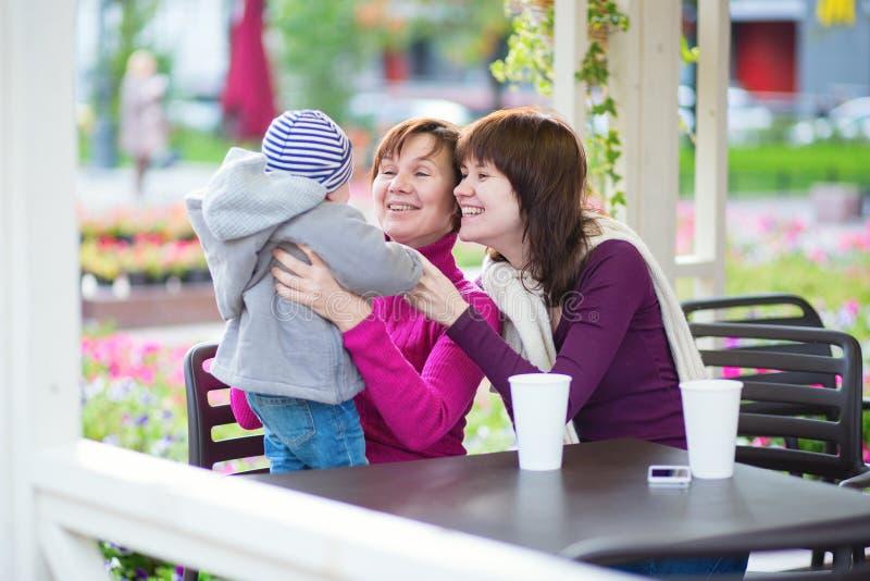 Grand-mère, mère et petit fils en café photo stock