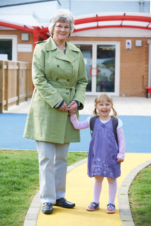 Grand-mère portant la petite-fille à l'école photos libres de droits
