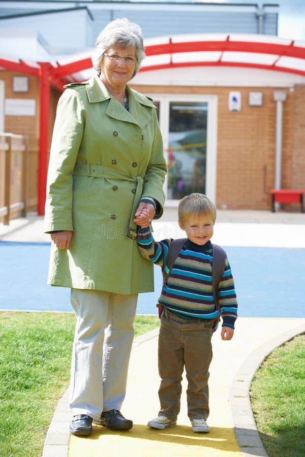Grand-mère portant le petit-fils à l'école photographie stock libre de droits