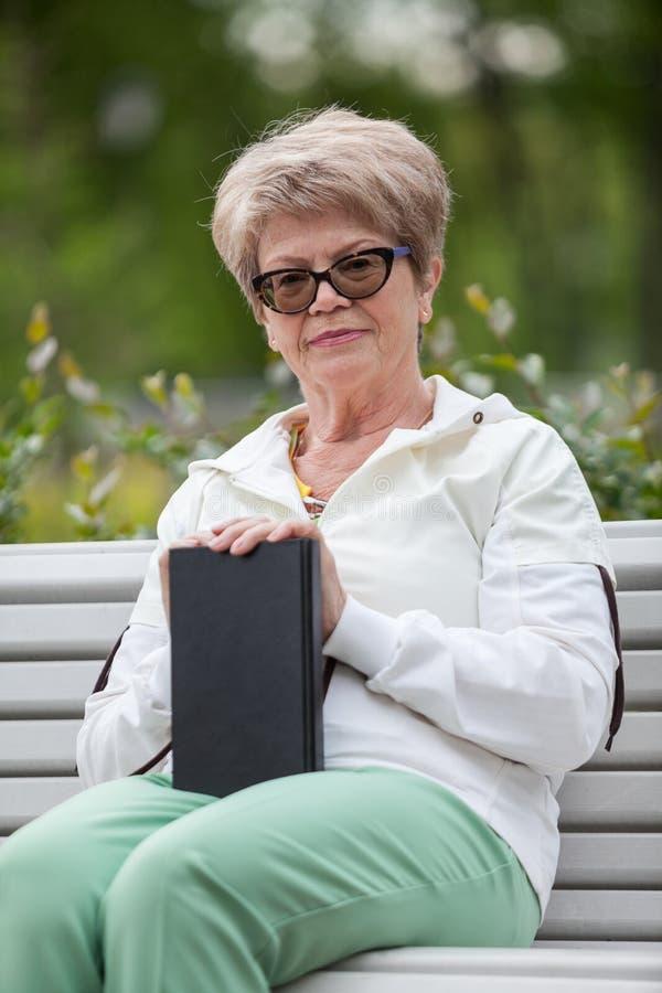 Grand-mère supérieure avec le livre noir dans des mains se reposant sur le banc en parc, regardant l'appareil-photo images stock