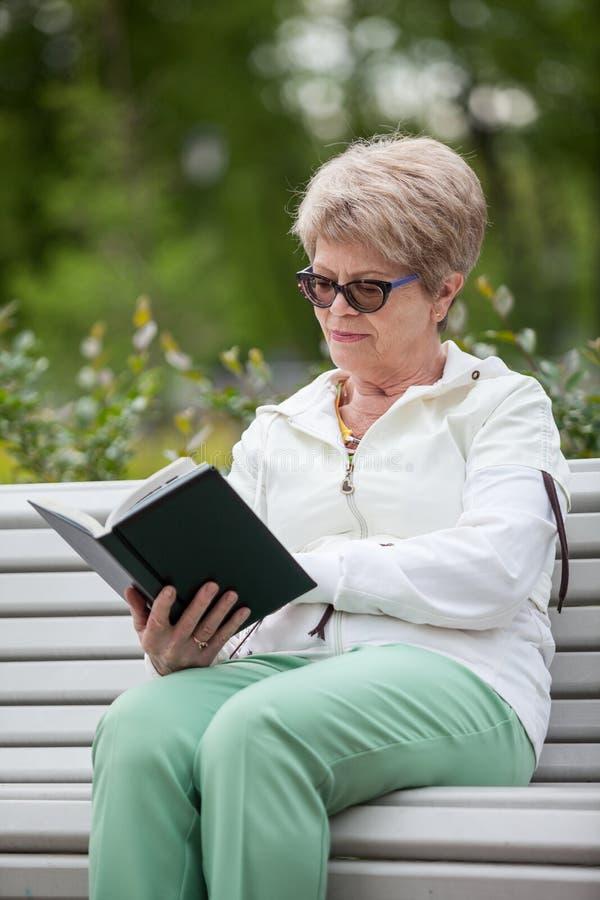 Grand-mère supérieure lisant le livre noir tout en se reposant sur le banc en parc photographie stock