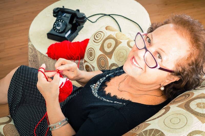 Grand-mère supérieure s'asseyant appréciant son tricotage photographie stock