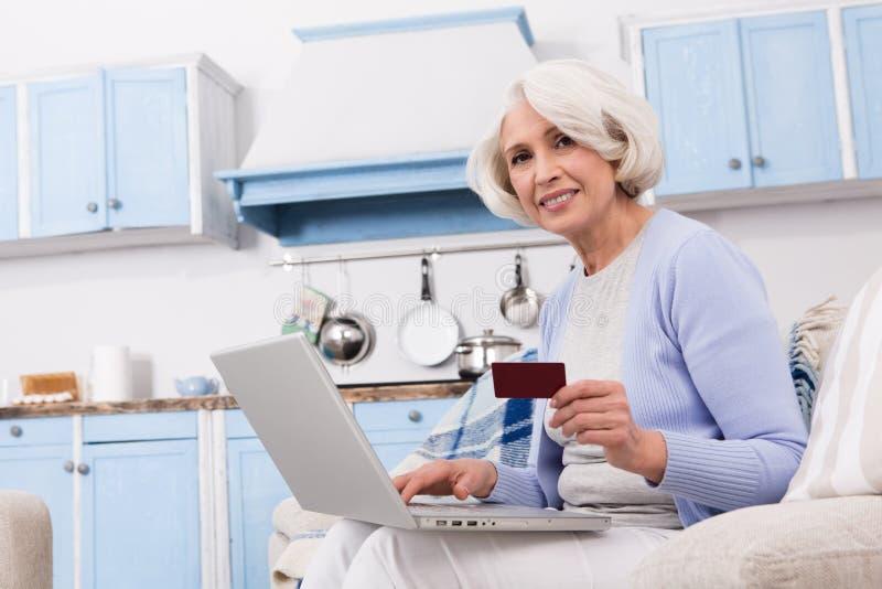 Grand-mère visitant le magasin en ligne image stock
