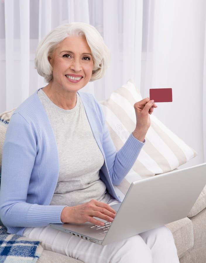 Grand-mère visitant le magasin en ligne images stock