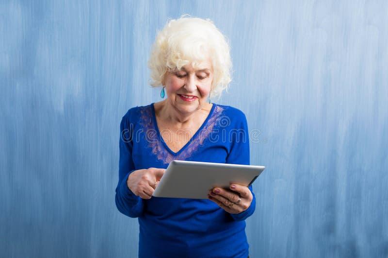 Grand-maman apprenant comment utiliser le comprimé photos stock