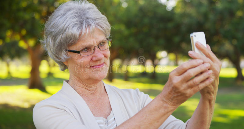 Grand-maman de hanche prenant des selfies au parc photos stock