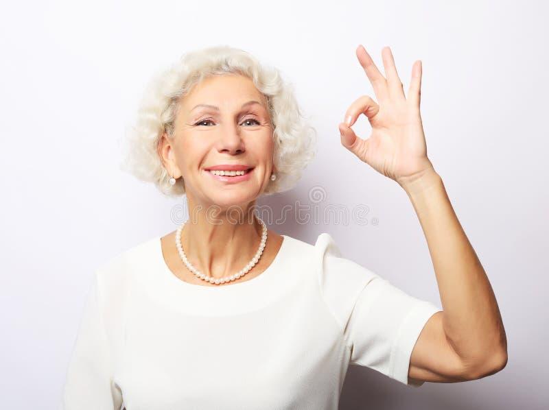 Grand-maman de mamie de grand-mère, elle montre le signe correct, d'isolement sur le fond blanc images libres de droits