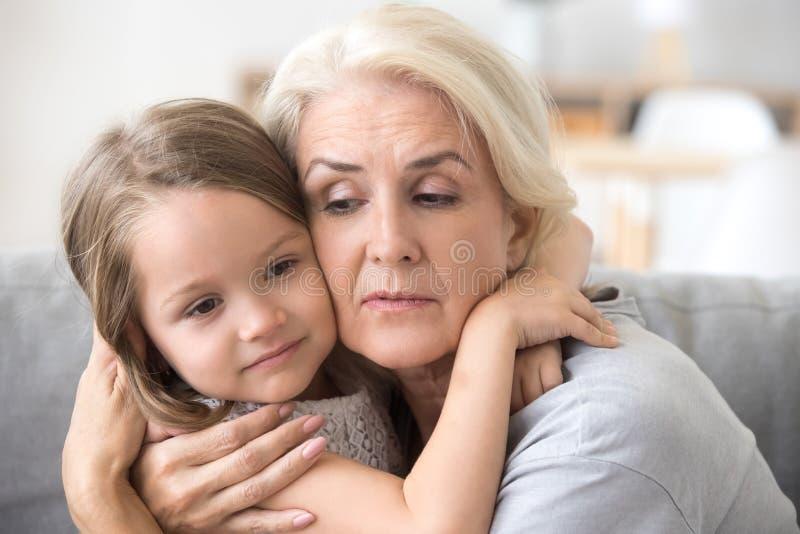 Grand-maman et petite-fille s'asseyant sur l'embrassement de divan image libre de droits
