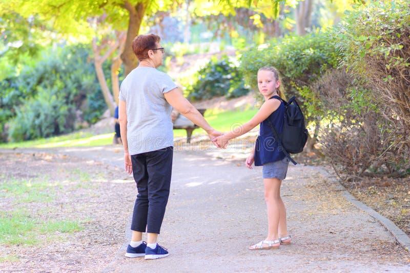 Grand-maman heureuse et petite-fille marchant à l'école sur la rue en parc d'automne images stock