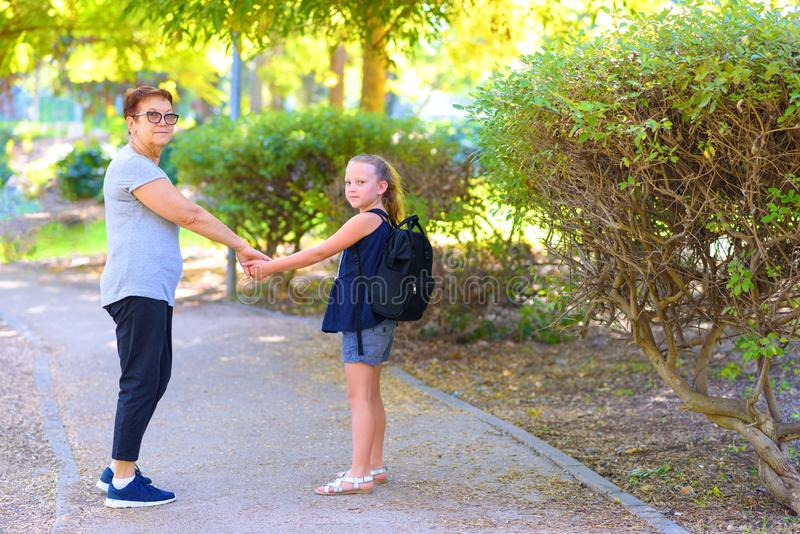 Grand-maman heureuse et petite-fille marchant à l'école sur la rue en parc d'automne image stock