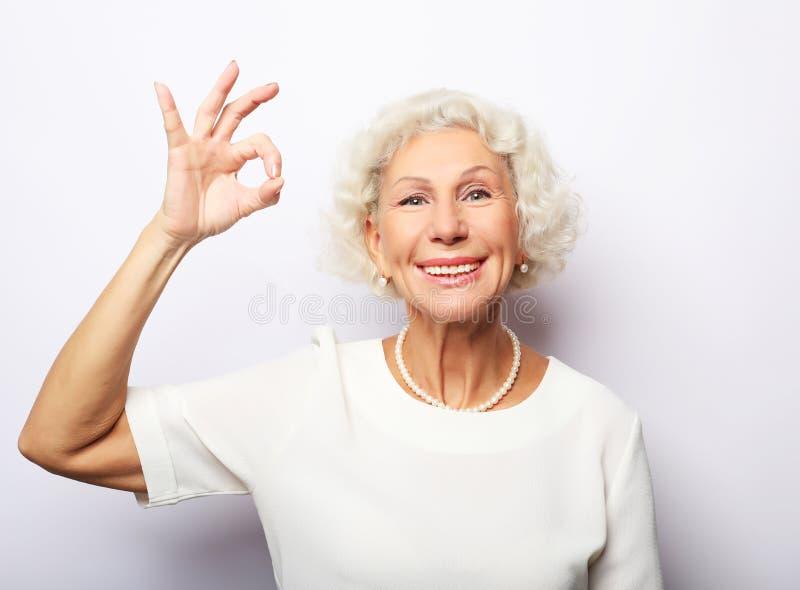 Grand-maman mûre de mamie de grand-mère de dame, elle montre le signe correct photo libre de droits