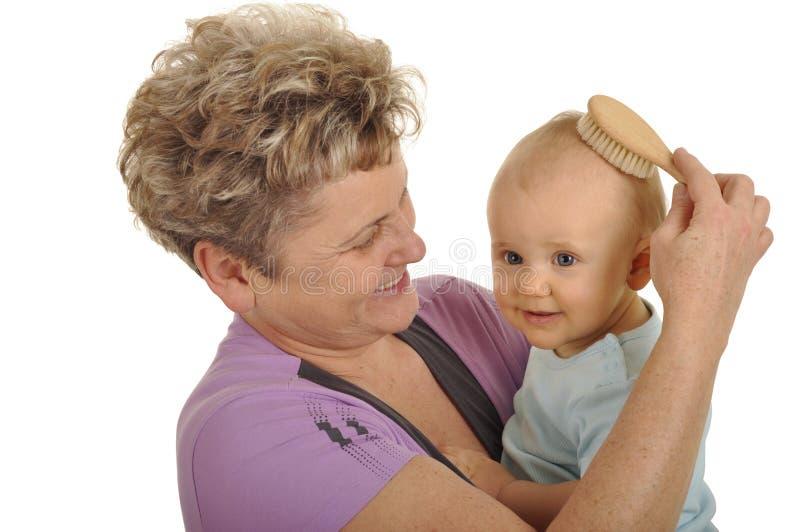 Grand-maman peignant l'enfant image stock