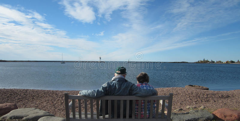 Grand Maris Harbor. Two people are sitting on a bench looking at the Grand Maris harbor royalty free stock photos