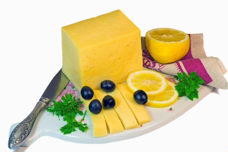 Grand morceau de fromage, de citron et d'olives sur un fond blanc. images stock