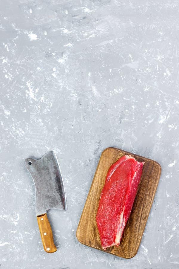 Grand morceau frais de boeuf sur une planche à découper en bois ronde avec la hache de cuisine Vue supérieure sur le fond concret image stock