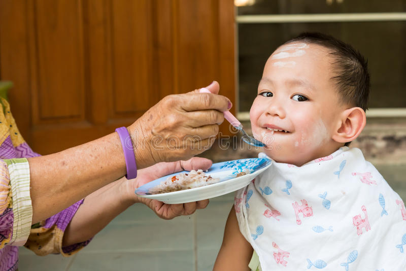 Grand mother feeding food to Thai baby boy royalty free stock photos