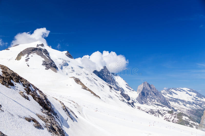 Grand Motte glacier in summer. Mountain and glacier Grand Motte in the clouds. Ski tow and summer skiing area of Tignes royalty free stock photography