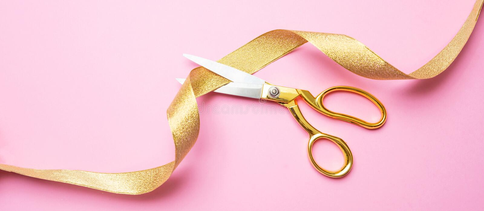 Grand opening. Gold scissors cutting golden ribbon, pink background, banner stock photos