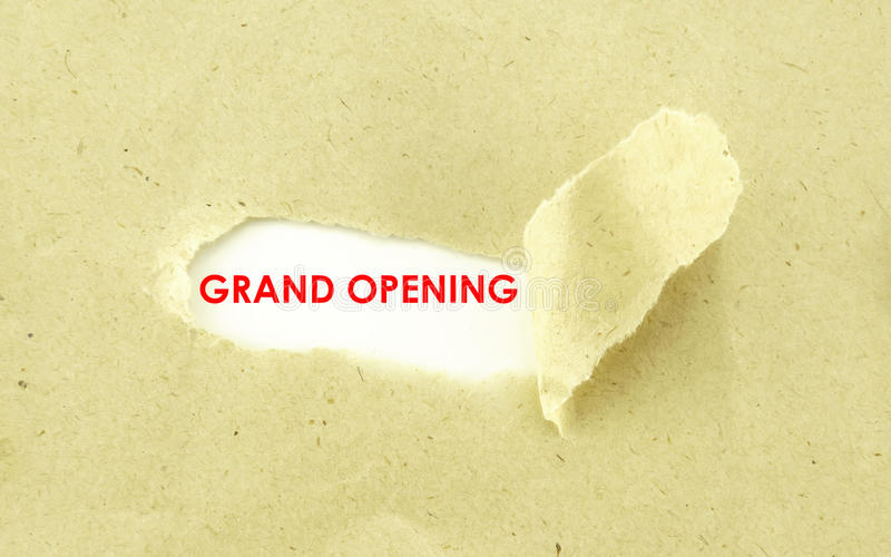 GRAND OPENING. Text GRAND OPENING appearing behind torn light brown envelope stock images