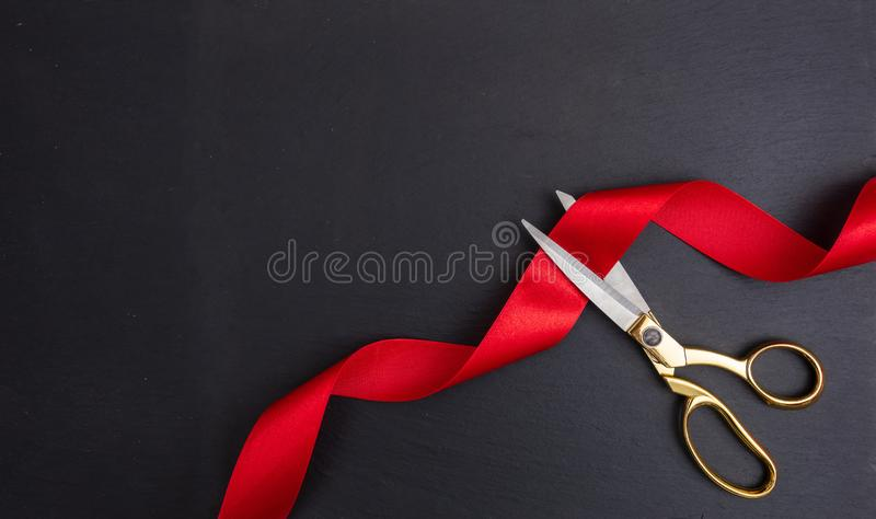 Grand opening. Top view of gold scissors cutting red silk ribbon against black background. Copy space stock photos