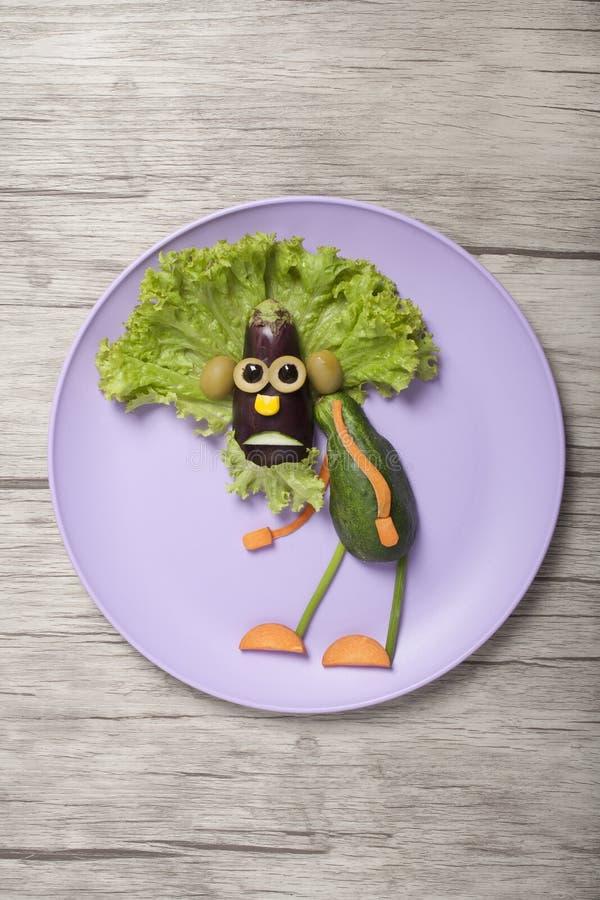 Grand-père aux légumes amusants abattu sur les assiettes et les planches photographie stock libre de droits