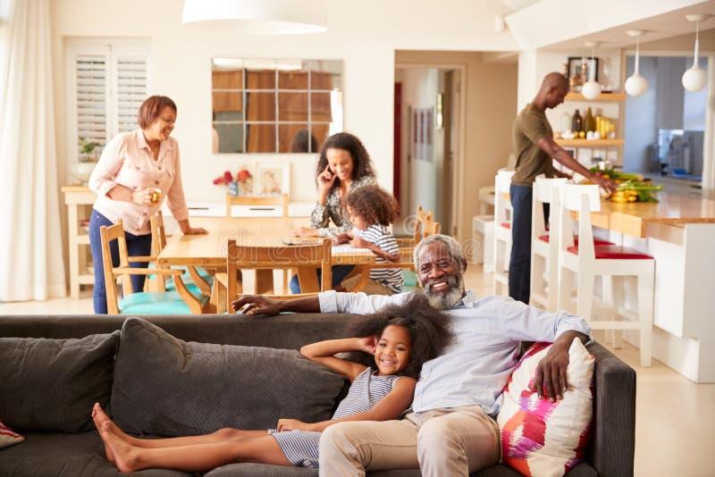 Grand-père avec la petite-fille s'asseyant sur Sofa At Home Watching Movie avec la famille à l'arrière-plan image stock