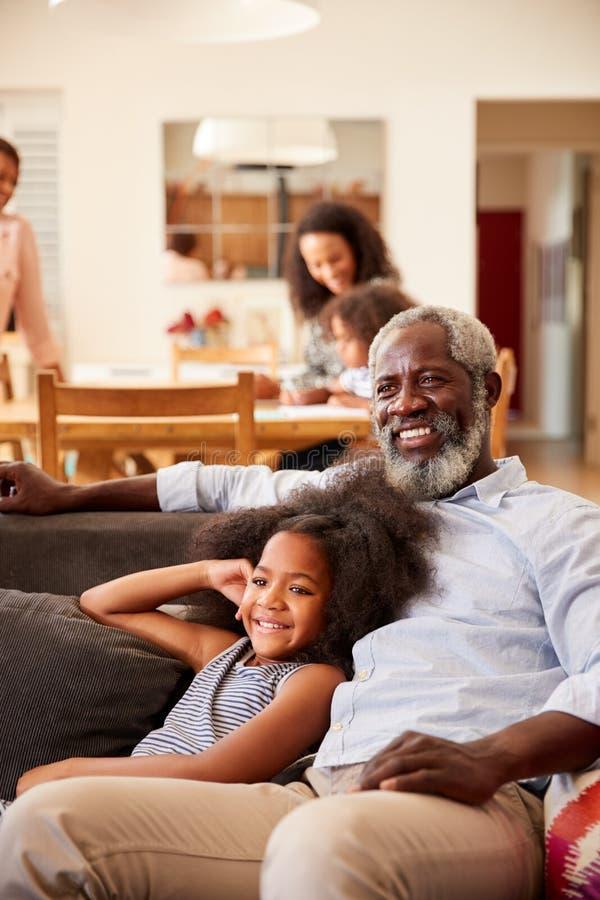 Grand-père avec la petite-fille s'asseyant sur Sofa At Home Watching Movie avec la famille à l'arrière-plan photographie stock