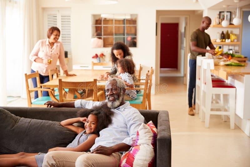 Grand-père avec la petite-fille s'asseyant sur Sofa At Home Watching Movie avec la famille à l'arrière-plan images libres de droits