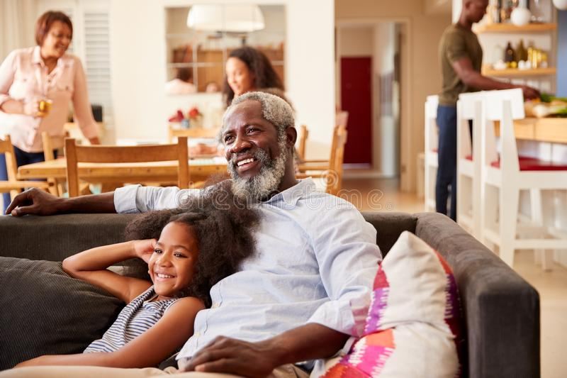 Grand-père avec la petite-fille s'asseyant sur Sofa At Home Watching Movie avec la famille à l'arrière-plan photos libres de droits