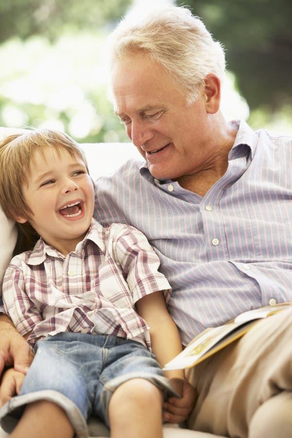 Grand-père avec le petit-fils lisant ensemble sur le sofa photo libre de droits