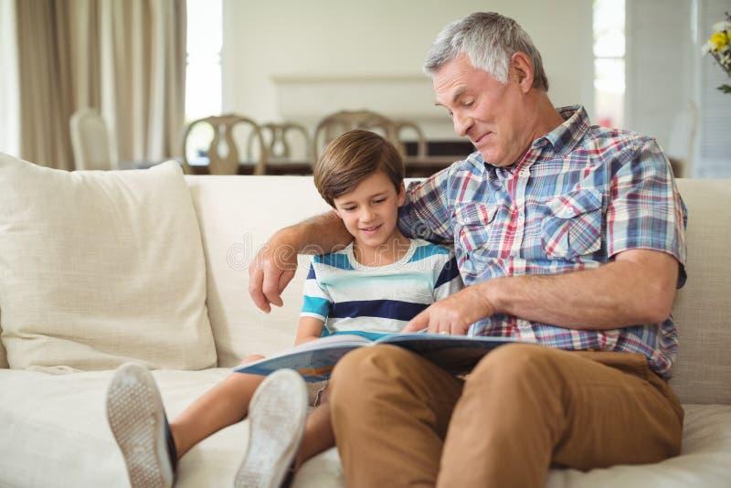 Grand-père avec son livre de lecture de petit-fils sur le sofa image stock