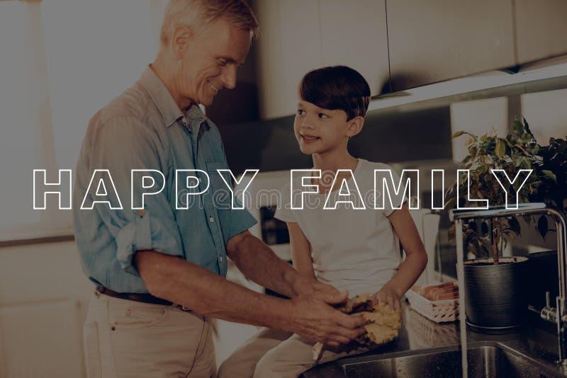 Grand-père dans la chemise Famille heureuse faisant cuire la salade photo libre de droits