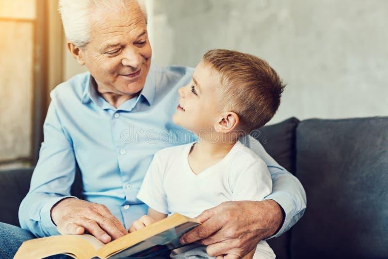Grand-père de soin lisant un livre à son petit-fils images stock