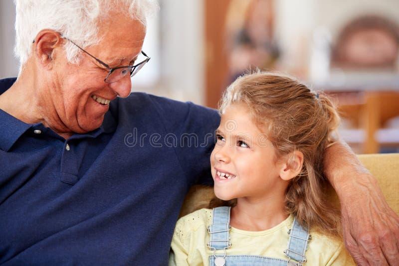 Grand-père de sourire s'asseyant avec la petite-fille sur Sofa At Home photographie stock