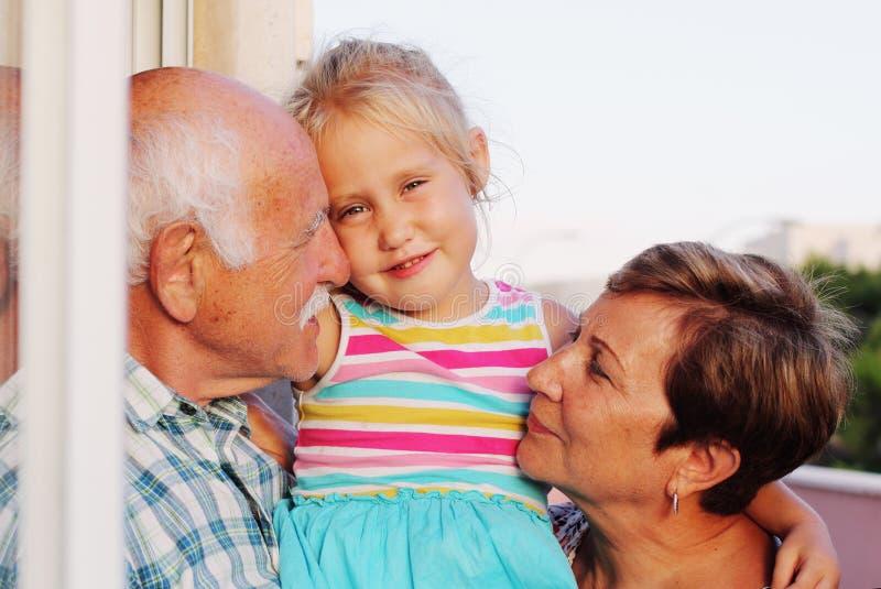 Grand-père et grand-mère tenant la petite-fille photo stock