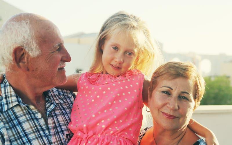 Grand-père et grand-mère tenant la petite-fille images stock